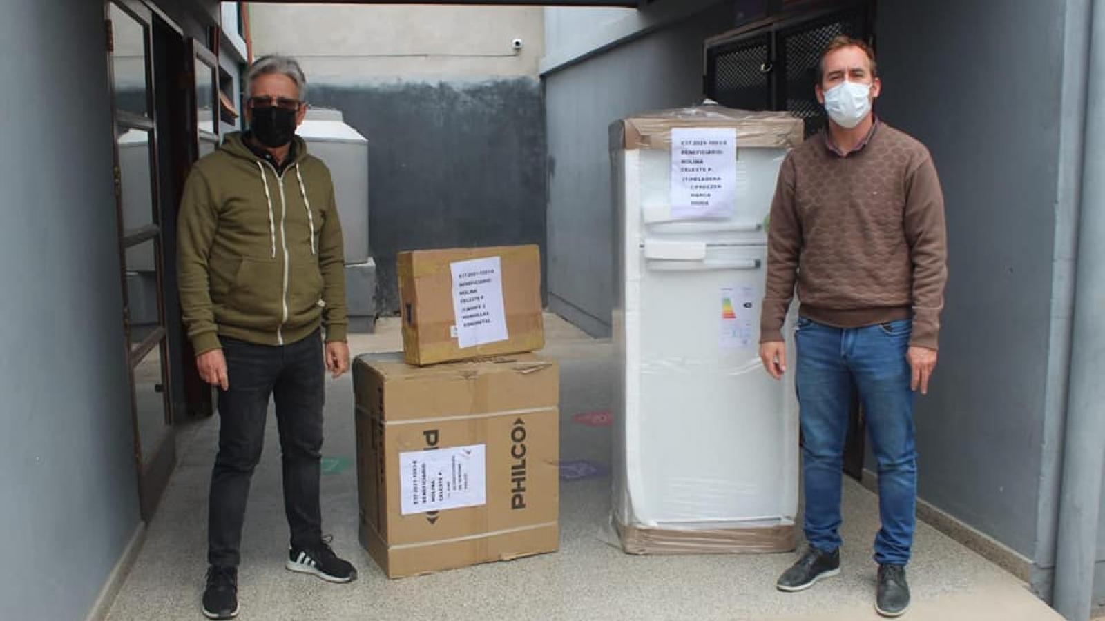 El presidente Lorenzo y el intendente García entregando heladera y aire acondicionado