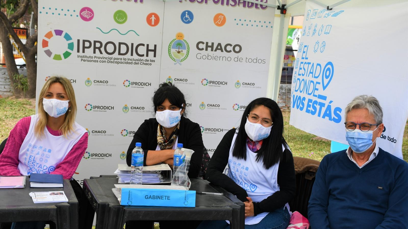El presidente Lorenzo junto a trabajadoras del IPRODICH sonríen a cámara en el stand de El Estado donde vos estás