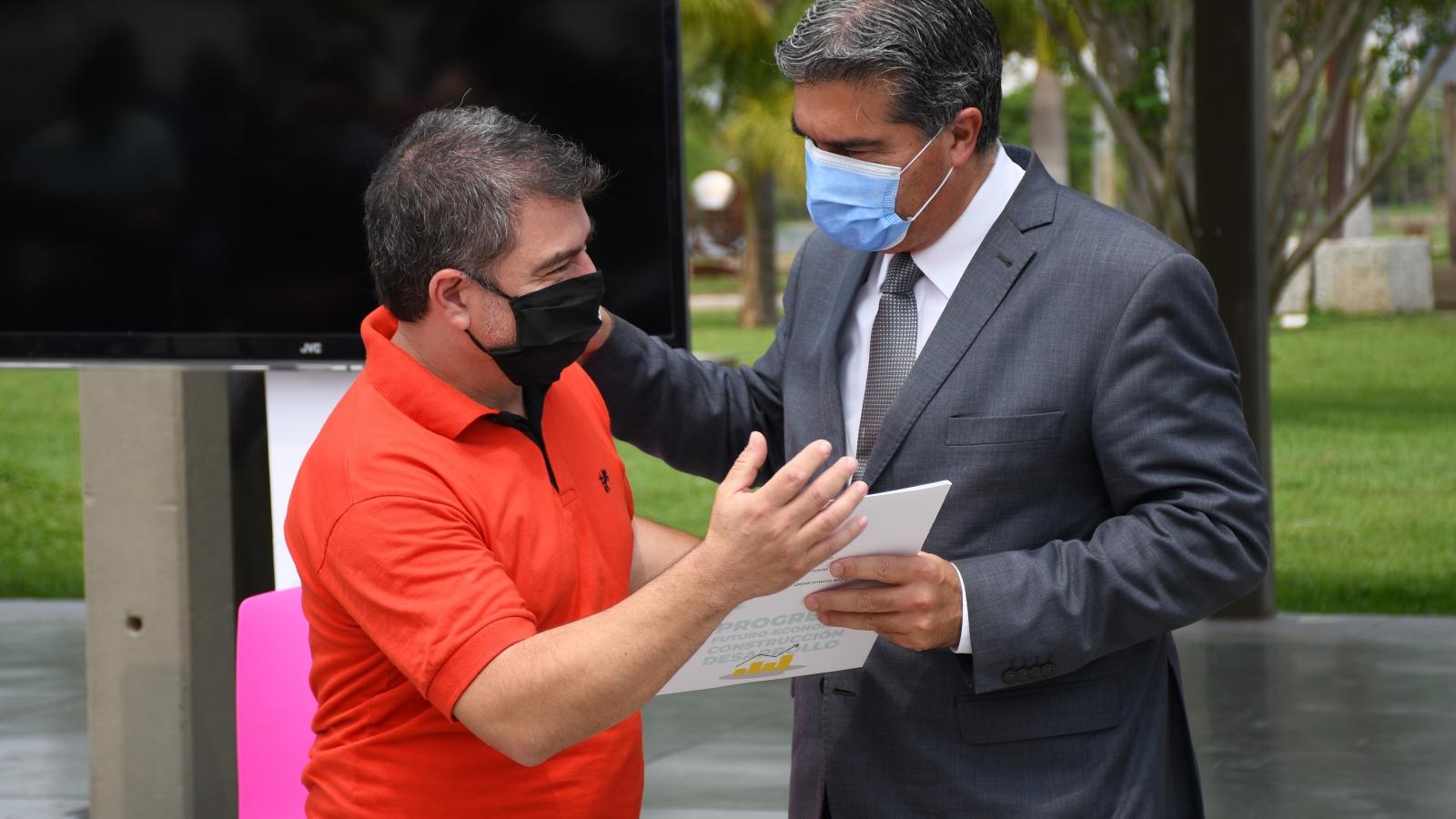 El gobernador Capitanich entregando la tarjeta del Programa Tuya Reactiva