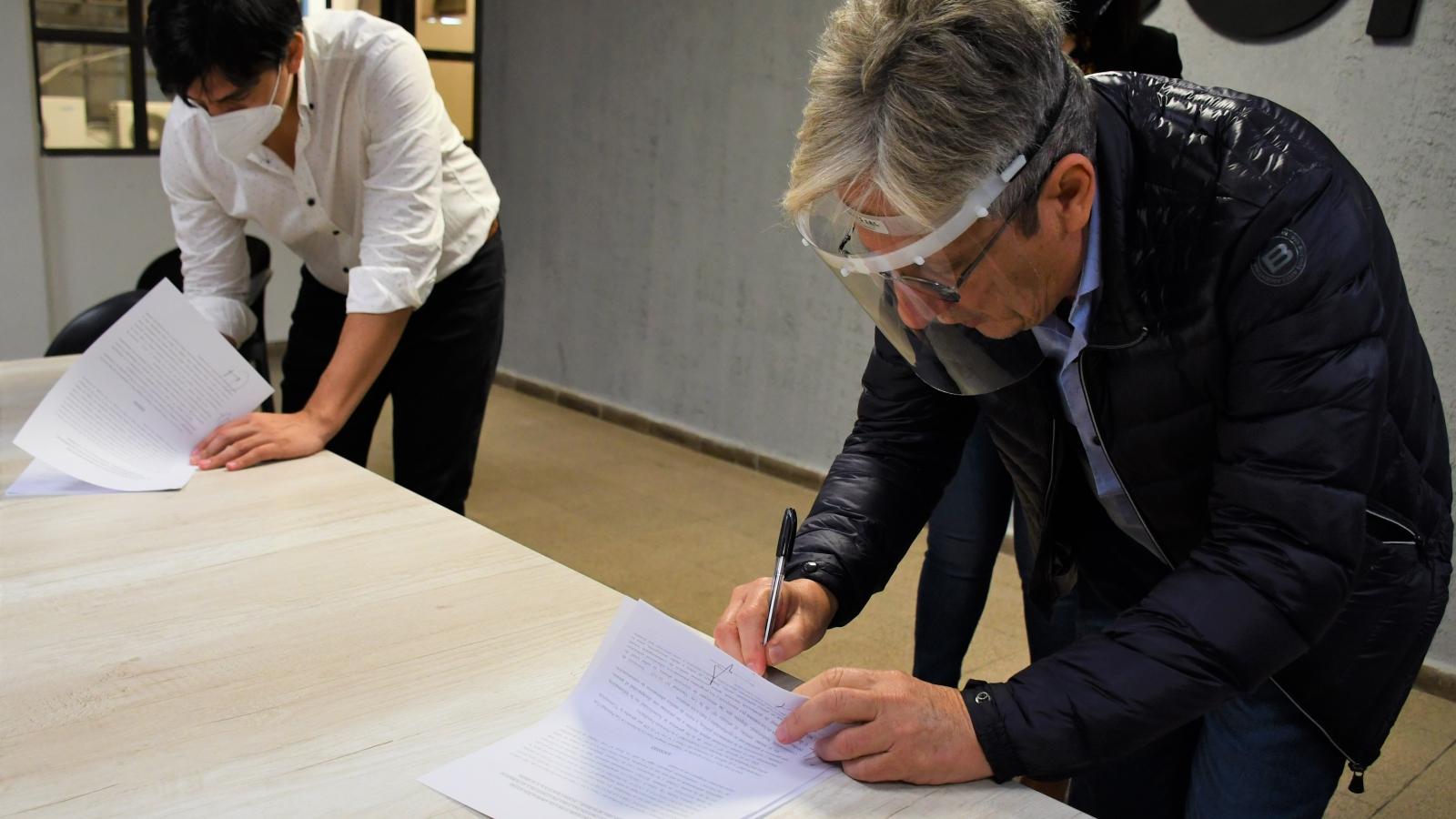 El presidente del IPRODICH, Lorenzo y el titular de ECOM, Vazquez, firmando convenio