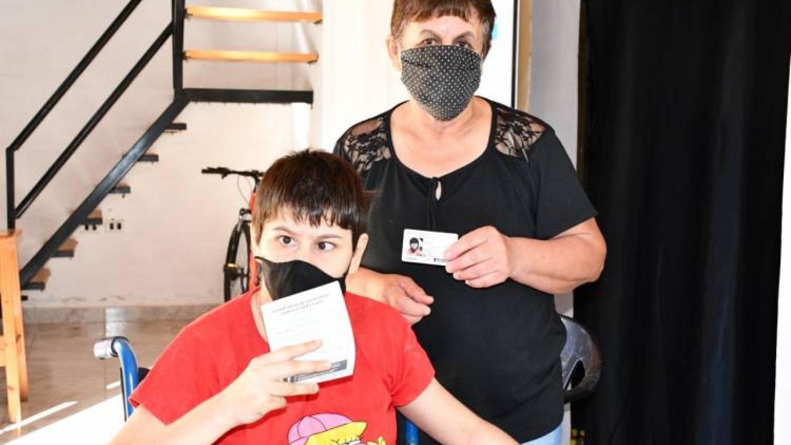 Persona en silla de ruedas muestra su carnet de vacunación anti COVID