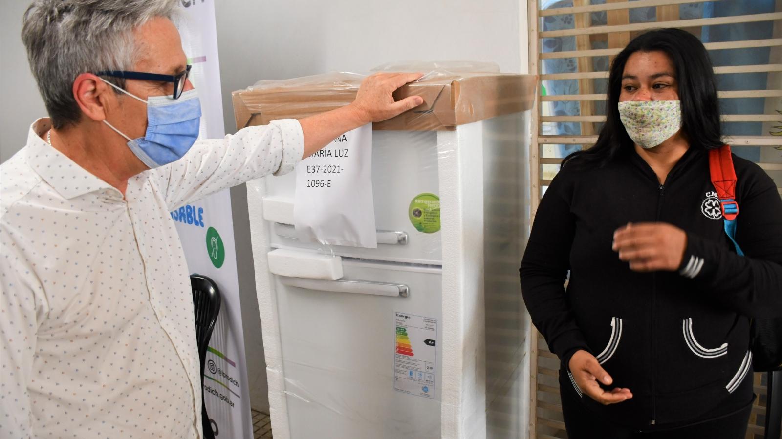 El presidente Lorenzo entregando una heladera a beneficiaria