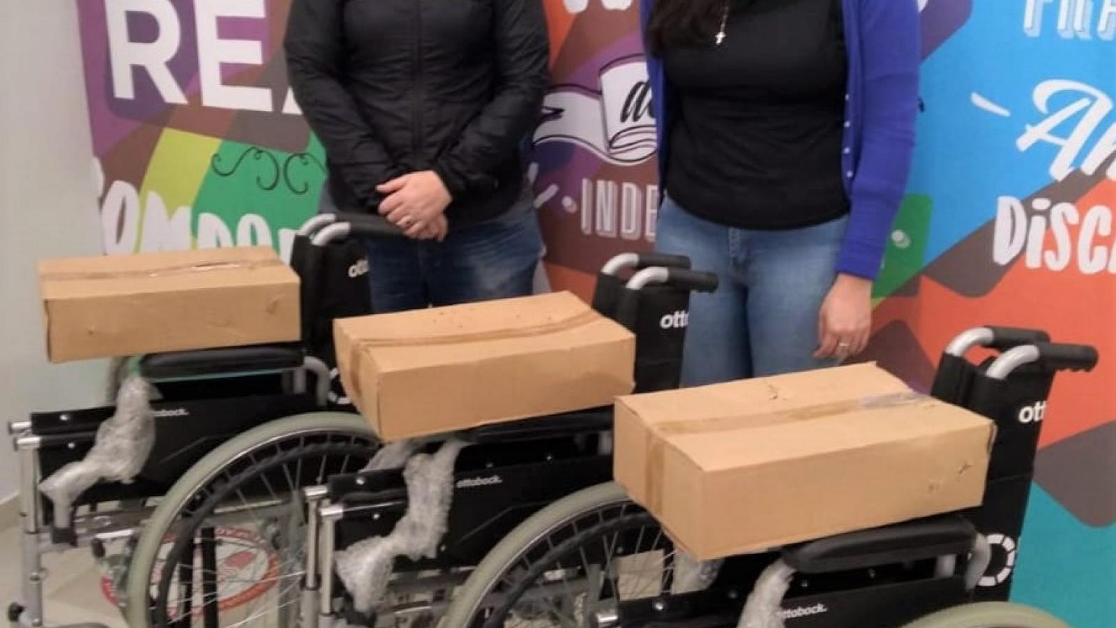 Trabajadores del IPRODICH entregando tres sillas de ruedas